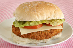 Chicken fillet burger in a bun. Chicken fillet in a bun with cheese lettuce and tomato royalty free stock image