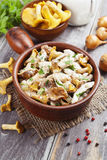 Chicken fillet with chanterelles and cream. In a pan on the table royalty free stock image
