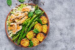 Chicken fillet cooked on a grill with a garnish of asparagus and baked potatoes. Dietary menu. Healthy food. Flat lay. Top view stock photography