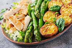 Chicken fillet cooked on a grill with a garnish of asparagus and baked potatoes. Dietary menu. Healthy food royalty free stock images