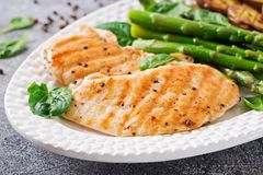 Chicken fillet cooked on a grill with a garnish of asparagus and baked potatoes. Dietary menu. Healthy food royalty free stock photography