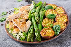 Chicken fillet cooked on a grill with a garnish of asparagus and baked potatoes. Dietary menu. Healthy food stock photo