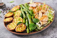 Chicken fillet cooked on a grill with a garnish of asparagus and baked potatoes. Dietary menu. Healthy food royalty free stock photos