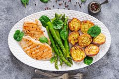 Chicken fillet cooked on a grill with a garnish of asparagus and baked potatoes. royalty free stock image