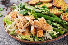 Chicken fillet cooked on a grill with a garnish of asparagus and baked potatoes. Dietary menu. Healthy food stock image