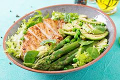 Chicken fillet cooked on a grill with a garnish of asparagus and grilled avokado. Dietary menu. Healthy food stock photos