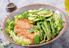 Chicken fillet cooked on a grill with a garnish of asparagus and grilled avokado. Dietary menu. Healthy food royalty free stock photos