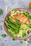 Chicken fillet cooked on a grill with a garnish of asparagus and grilled avokado. Dietary menu. Healthy food. Flat lay. Top view stock photo