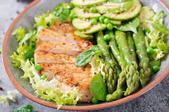 Chicken fillet cooked on a grill with a garnish of asparagus and grilled avokado. Dietary menu. Healthy food stock images