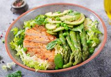 Chicken fillet cooked on a grill with a garnish of asparagus and grilled avokado. Dietary menu. Healthy food stock photo