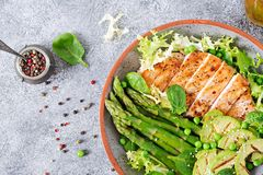 Chicken fillet cooked on a grill with a garnish of asparagus and grilled avokado. Dietary menu. Healthy food. Flat lay. Top view stock image