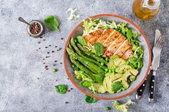 Chicken fillet cooked on a grill with a garnish of asparagus and grilled avokado. Dietary menu. Healthy food. Flat lay. Top view stock images