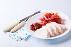 Chicken fillet with cranberry relish. And tomato salad, light blue background, closeup Stock Photography