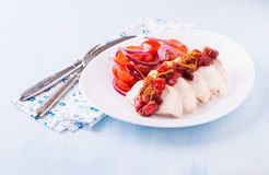 Chicken fillet with cranberry relish. And tomato salad, light blue background, closeup Royalty Free Stock Photos