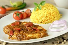 Chicken fillet with curry sauce. Chicken with curry sauce and rice coloured with saffron stock image