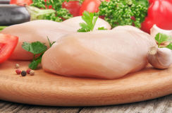 Chicken fillet on a cutting board with vegetables. Closeup Royalty Free Stock Image