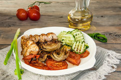 Chicken fillet, fresh cucumbers, artichokes and peppers on white ceramic pan. The horizontal frame. Stock Images