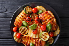 Chicken fillet grilled with pineapple, zucchini and tomatoes in Royalty Free Stock Photos