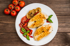 Chicken fillet grilled with vegetables. Wooden background. Top view Stock Photo