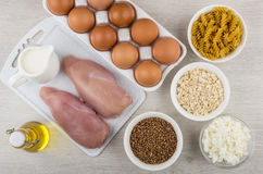 Chicken fillet, milk, cottage cheese, eggs, oil, pasta and cerea. Raw chicken fillet, milk, cottage cheese, eggs, vegetable oil, pasta and cereals on wooden Royalty Free Stock Photos