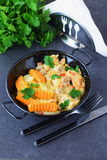 Chicken fillet with mushrooms in a creamy souce and fried sweet potato in a black metal bowl on a grey abstract Stock Images