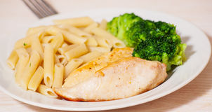 Chicken fillet with penne pasta and broccoli Stock Photos