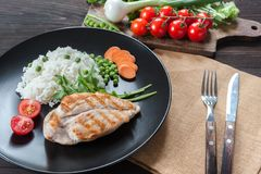 Chicken fillet on plate with rice stock image