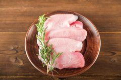 Chicken fillet with rosemary on a wooden plate on a textural table. Raw turkey meat and peppercorns close-up and copy space.  stock photos