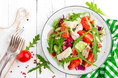 Chicken fillet salad with tomato, lettuce, cucumber and arugula leaves. Fresh vegetable salad with chicken meat. Healthy food. Whi. Te wooden background. Top Royalty Free Stock Photo