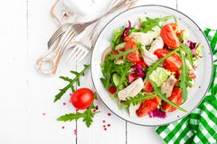 Chicken fillet salad with tomato, lettuce, cucumber and arugula leaves. Fresh vegetable salad with chicken meat. Healthy food. Whi. Te wooden background. Top Stock Photography