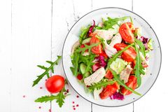 Chicken fillet salad with tomato, lettuce, cucumber and arugula leaves. Fresh vegetable salad with chicken meat. Healthy food. Whi. Te wooden background. Top Royalty Free Stock Images