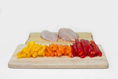 Chicken fillet seasoned with various spices on a cutting board with a side dish of vegetables Stock Images