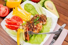Chicken fillet with vegetable. Chicken fillet with avocado and some vegetable on the side tomato, cucumber, bell pepper on a white background eaten with a fork Stock Photos