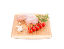 Chicken fillet and vegetables on cutting board. Royalty Free Stock Photography