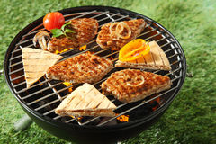Chicken fillets and bread grilling on a BBQ Royalty Free Stock Photos
