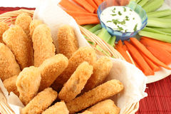 Chicken fingers. Basket of crispy chicken fingers with platter of vegetables and dip Stock Image