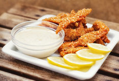Chicken fingers served with tartar sauce and lemon slices Stock Image