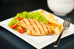 Chicken, French fries and salad Stock Images