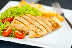 Chicken, French fries and salad Royalty Free Stock Photography