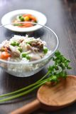 Chicken fricassee with green pea served with boiled rice on a wooden background. Chicken fricassee with green pea served with boiled rice on a wooden background Stock Images