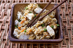 Chicken Fried Rice. In a wooden bowl with chopsticks on a woven mat Royalty Free Stock Photo