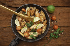 Chicken fried in skillet with wooden spatula stock photo