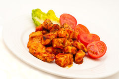 Chicken fried in tomato sauce isolated on white Stock Images