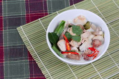 Chicken and galangal in coconut milk soup and herb on bamboo red green. Side view Stock Image
