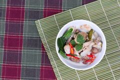 Chicken and galangal in coconut milk soup and herb on bamboo red green.  Top view Royalty Free Stock Image