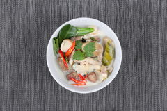 Chicken and galangal in coconut milk soup and herb on black. Top view Stock Images