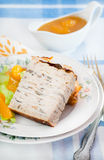 Chicken galantine stuffed with pancakes. Tangerine sauce on side Royalty Free Stock Photography