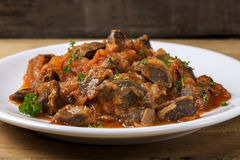 Chicken gizzard stew on plate with herbs Royalty Free Stock Photo
