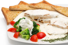 Chicken with gorgonzola, vegetables and bread on the plate Stock Images