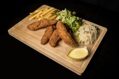 Chicken Goujons served on wood stock photography